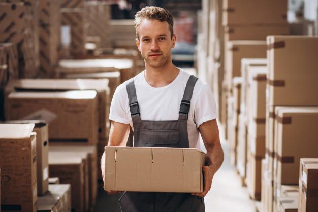 jovem-que-trabalha-em-um-armazem-com-caixas_1303-16605